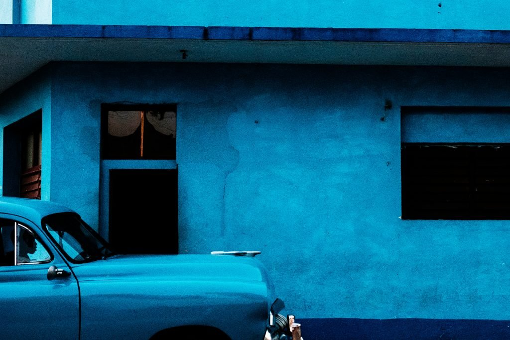 Street photography Image. Blue classic car in front of a blue building found in Havana, Cuba. Travel Photography by Dom & Liam Shaw
