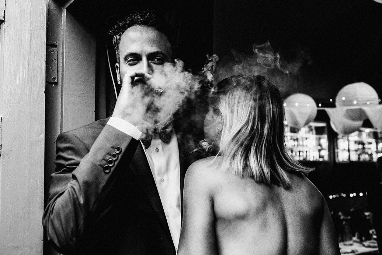 Man in suit & bow tie smokes a cigar with smoke flying around him. A woman in a strapless dress is to his right with her back turned to the camera. Event photography by London Portrait & event photographers York Place Studios