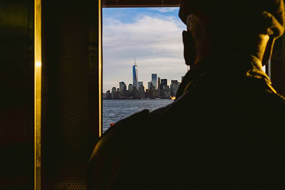 Man silhouetted in window looking over at New York skyline from the Staten Island Ferry at sunrise. Golden sunlight hits him from the right of the frame. Photographed by London portrait & family photographers York Place Studios
