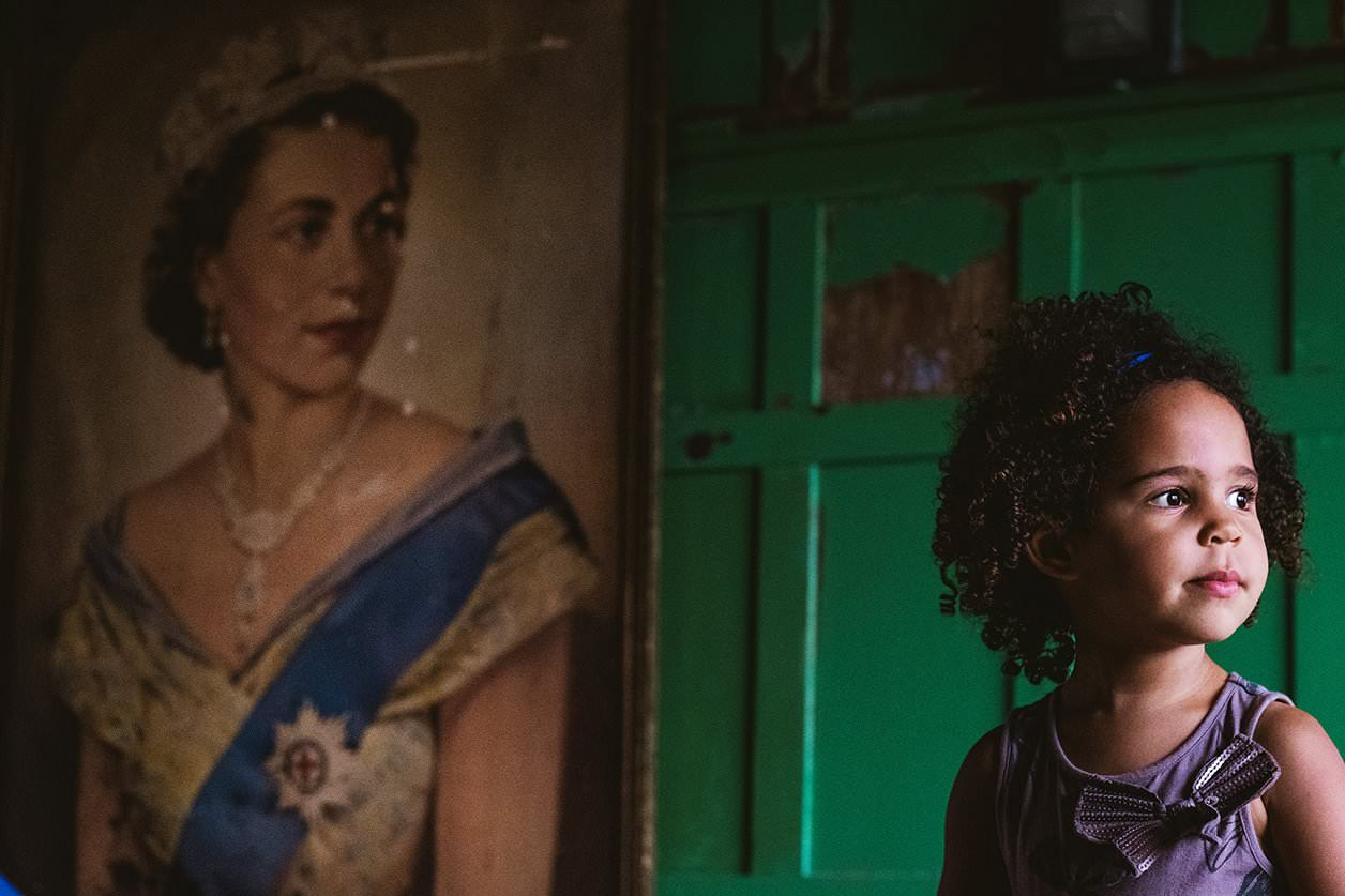 unposed portrait of a young girl on the right of the frame and a painted portrait of her majesty The Queen on the left of the frame. There is symmetry between the two as they face the same direction, share a similar facial expression and a bow on the little girl's dress looks similar to the medal attached to the queen's blue sash. Reportage style London portrait photography by photographers Dom & Liam Shaw of York Place Studios