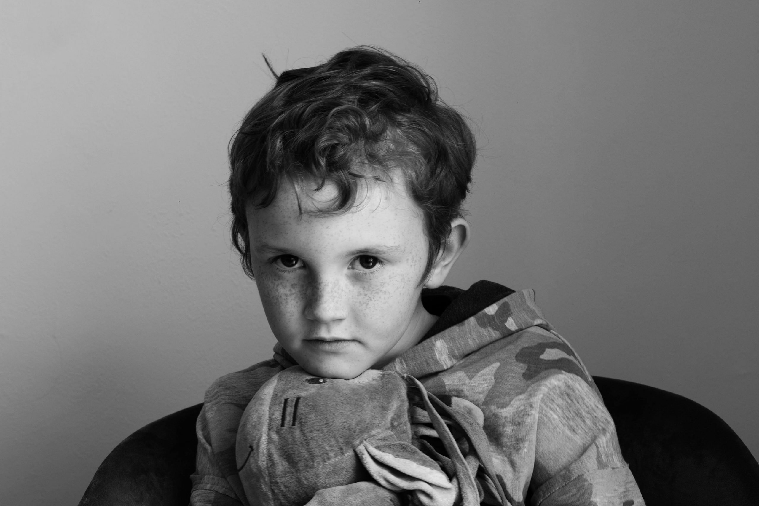 Young boy looks at the camera holding a horse toy. Monochrome headshot portrait photography by York Place