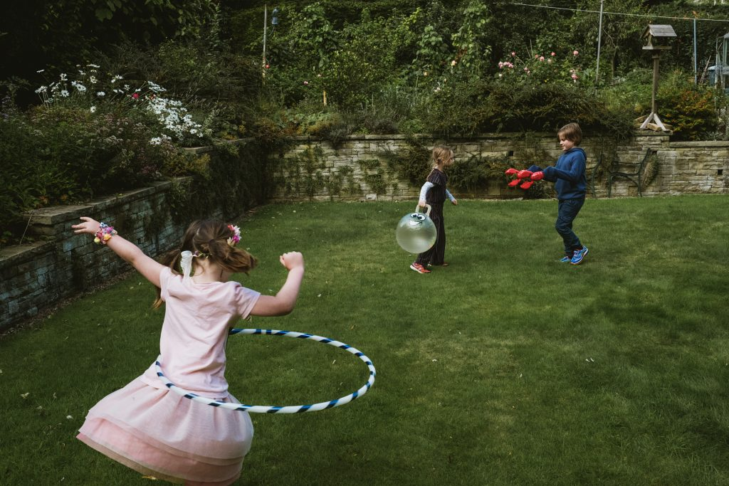 child using hula hoop whilst two siblings play in background